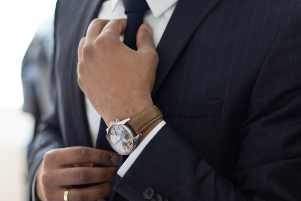 Close-up of person in suit adjusting tie